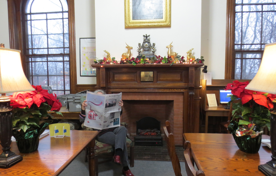 Image: someone reading a newspaper in front of a fireplace, framed by two long wooden tables with lamps and pointsetta