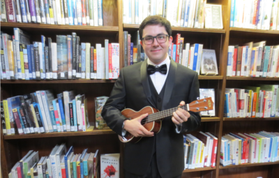image: young man in a tux holding a ukulele in front of bookshelves